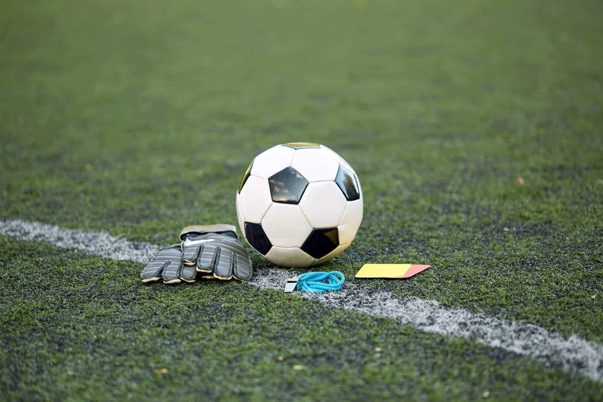 ball, gloves, whistle and cards on soccer field